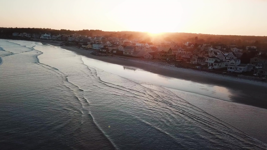 Drone clip of ocean waves and beach houses at sunset along the Maine coastline. Taken at Higgins Beach near Portland Maine.