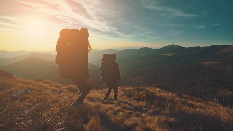 The hikers walking in the mountain on the sunrise background. slow motion