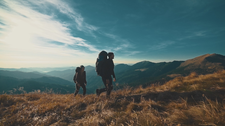 The couple walking on the mountain on a sunny background. slow motion | Shutterstock HD Video #1030416089