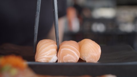 Asian woman eating sushi in japanese restaurant, young female holding chopsticks and eating salmon sushi in lunch time in summer. Lifestyle women eating traditional food concept. Slow motion shot.