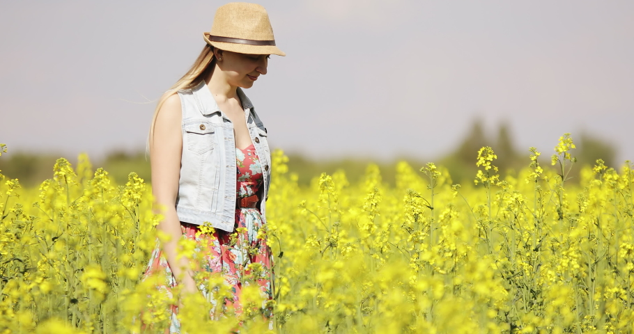 A young woman in a hat and dress walks through a yellow field in summer. Large blooming rapeseed field. #1030490099