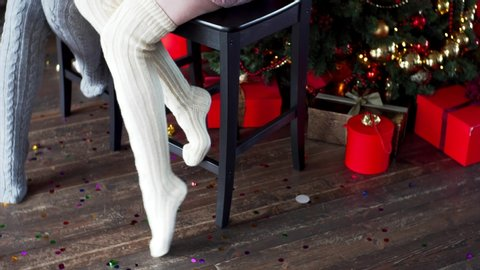 Sliding view of women's legs in warm stockings. Christmas decorations