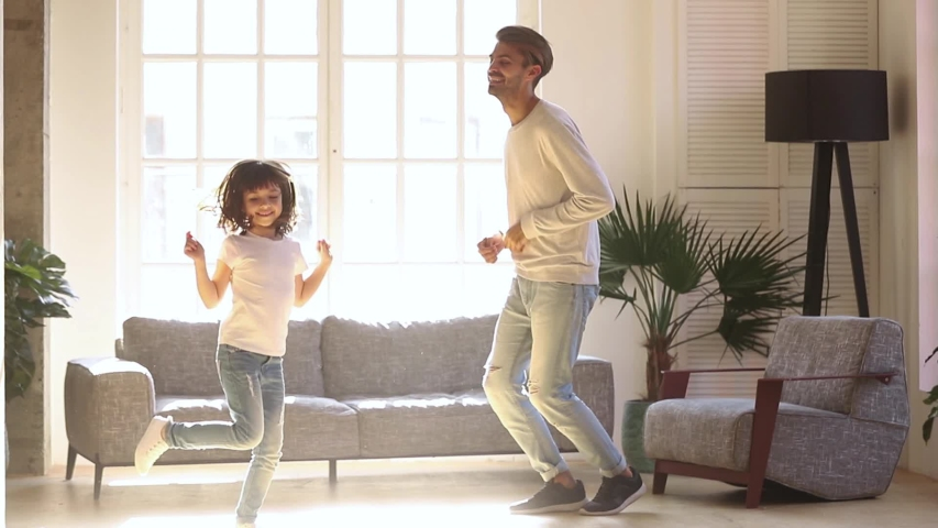 Happy family dad and kid daughter laughing jumping dancing in living room lit with sunlight, energetic child girl having fun with father moving to music play with parent at home enjoy funny activity | Shutterstock HD Video #1030504769