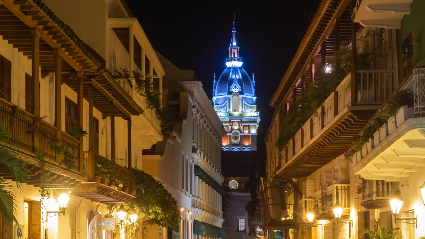 Cartagena de Indias, Colombia - December 10, 2018: Zoom out time lapse view of tourists on the streets of the Walled City showing Cartagena Cathedral at night in Cartagena de Indias, Colombia.