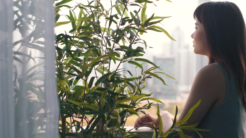 Young asian city life woman standing at room balcony and looking at green plant in apartment, eco living concept | Shutterstock HD Video #1030577489