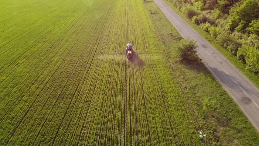 Aerial view of farming tractor spraying on field with sprayer, herbicides and pesticides at sunset. Farm machinery spraying insecticide to the green field, agricultural natural seasonal spring works. | Shutterstock HD Video #1030583999
