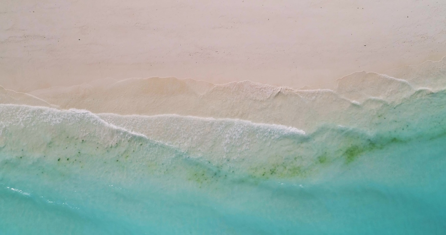 Aerial view of a transparent blue sea with beautiful waves at sunny day in summer. Tropical landscape from the air of ocean with azure water, sandy bottom at sunset. Top view from flying drone. Nature   Shutterstock HD Video #1030586519
