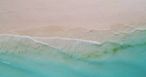 Aerial view of a transparent blue sea with beautiful waves at sunny day in summer. Tropical landscape from the air of ocean with azure water, sandy bottom at sunset. Top view from flying drone. Nature
