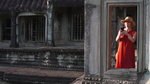Sliding view of young woman taking photo from gallery of Angkor Wat temple built in 12th century in Cambodia and dedicated to Vishnu. Cambodia
