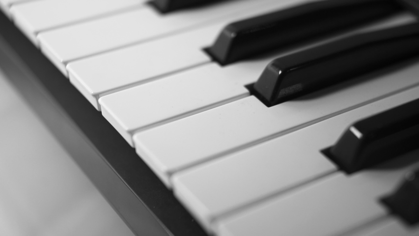 Close up pan across the black and white keys of an electronic keyboard piano | Shutterstock HD Video #1030638659