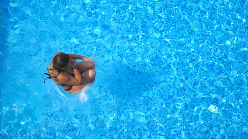 Top view of young woman jumping in pool and splashing crystal clear water. Unrecognizable girl resting and having fun on resort. Lady relaxing during summer vacation or holiday. Slow motion Close up | Shutterstock HD Video #1030854689