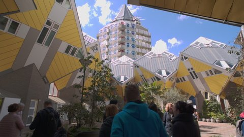 ROTTERDAM, HOLLAND - April 2019: Kubuswoningen, tourists walking through Cube house patio in Rotterdam, South Holland, the Netherlands. Innovative cube-shaped houses designed by architect Piet Blom.