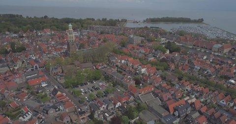 Aerial of traditional buildings and rooftops in historic Dutch town Enkhuizen in North Holland the Netherlands with the port and sea in the background