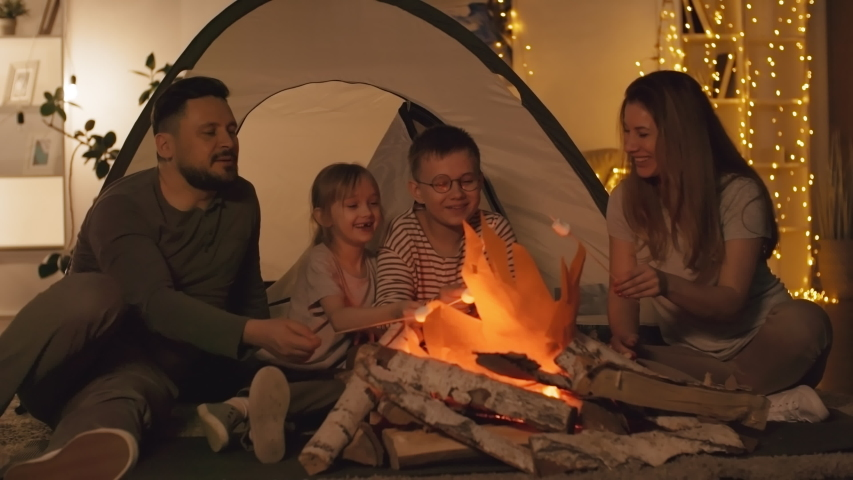 Lockdown of Caucasian man, woman and two kids sitting near artificial fire before tent in living room at night, roasting marshmallows on skewers and then eating them | Shutterstock HD Video #1030918799