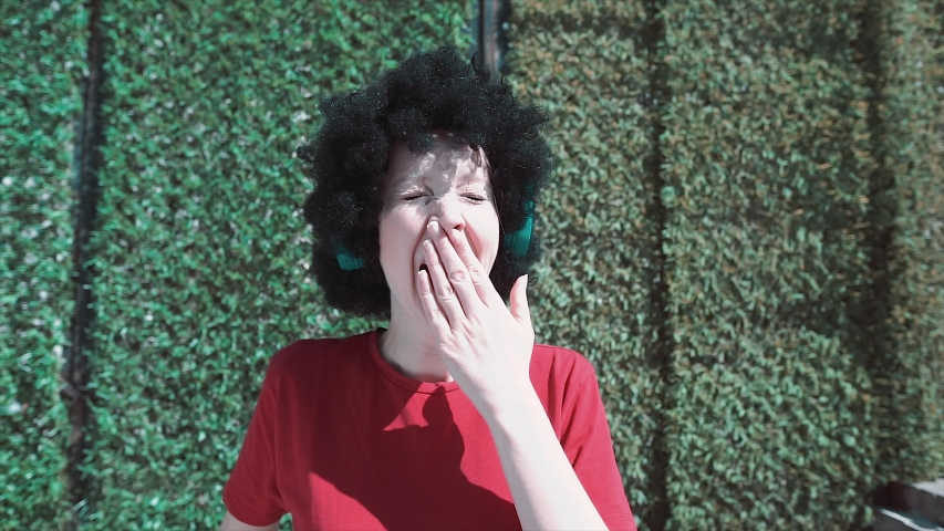 Tired Afro haired characteristic student is yawning. Yawning sleepy lady, girl with curly head.  | Shutterstock HD Video #1030971899