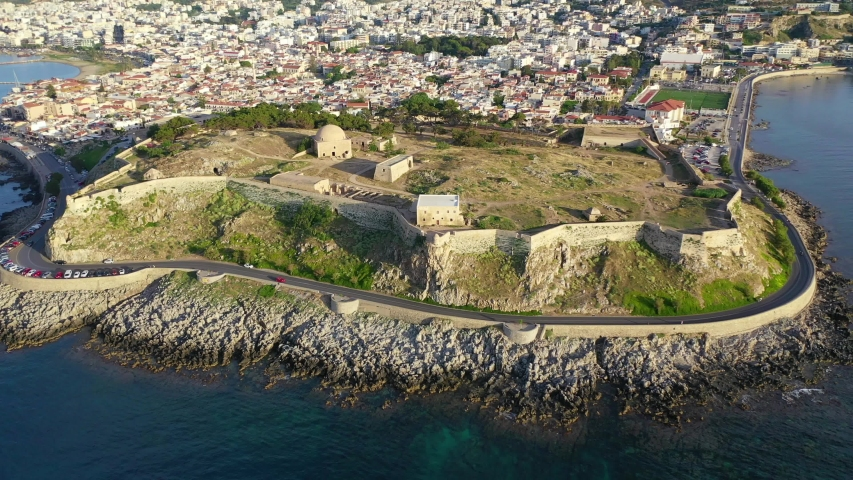 Aerial drone video of unique Venetian castle of Fortezza built on a hill called Paleokastro by the sea in the heart of picturesque city of Rethymno, Crete island, Greece | Shutterstock HD Video #1030983059