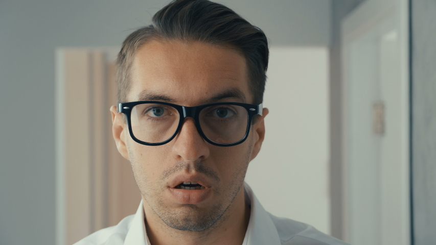 Portrait of young man is surprised and takes off his glasses in shock. He is worried about seeing | Shutterstock HD Video #1030983149