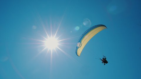 Extreme paraglider flying against a clear blue sky, sunbeam shines into camera. Man with instructor flies with parachute. 4k, slow motion.