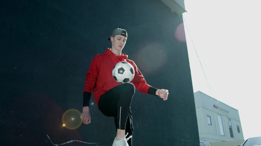 A young guy in a cap throws a soccer ball with his knees. Teenager warming up in the background of the building, playing football. The boy plays the ball with his knees.Street football. Slow motion,4K | Shutterstock HD Video #1031025419