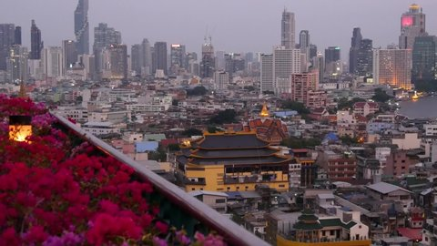 View of traditional and modern buildings of oriental city. Beautiful flowerbed against cityscape of traditional houses and skyscrapers on misty day on streets of Bangkok or Krungtep