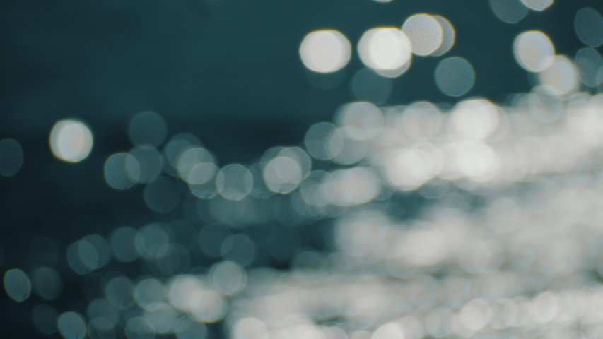 Bokeh sun glare reflected in water surface. Sunrays flickering in water stream. The shimmering small sea waves in sun. Abstract blurry out of focus bokeh background imagery. Slow motion, 4k footage.