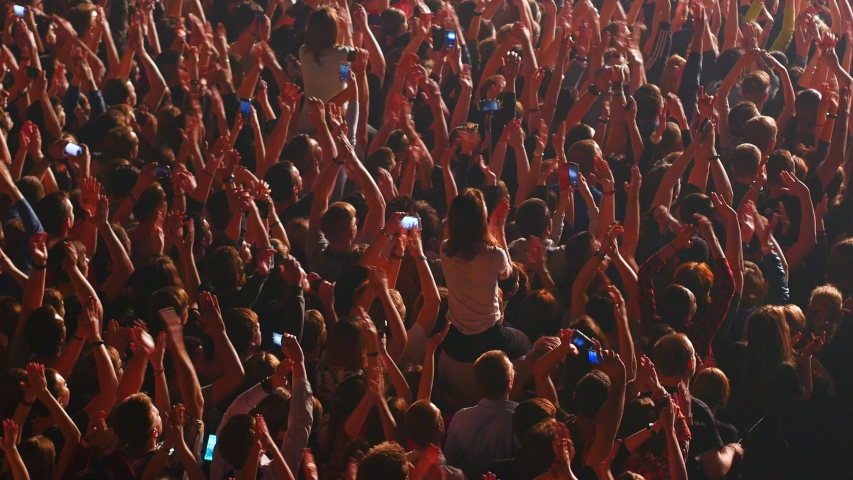 Crowd enjoys listening concert claps hands and takes photos | Shutterstock HD Video #1031102399