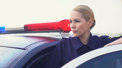 Confident policewoman looking into distance standing behind door of police car