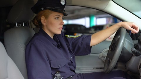 Tired policewoman taking off service cap sitting in patrol car, night shift