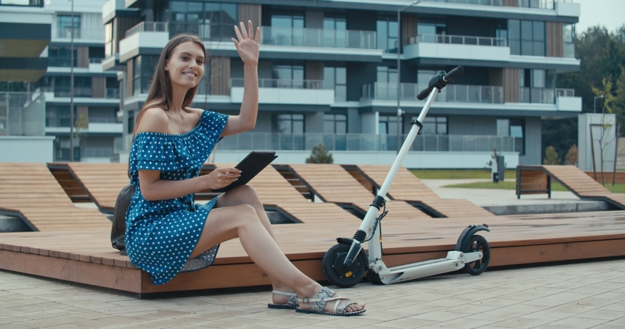 Woman sitting on bench among urban space and reading ebook using digital reader. Attractive girl with electric kick scooter waiting friend . 4K slow motion raw video footage 60 fps