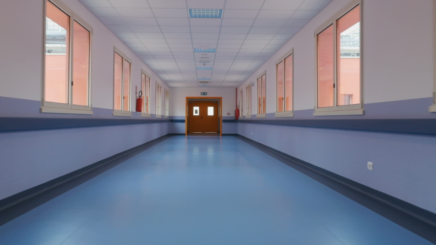 Long empty corridor of a large building, towards the exit. Passage through a long empty corridor to exit direction. First person view | Shutterstock HD Video #1031183609