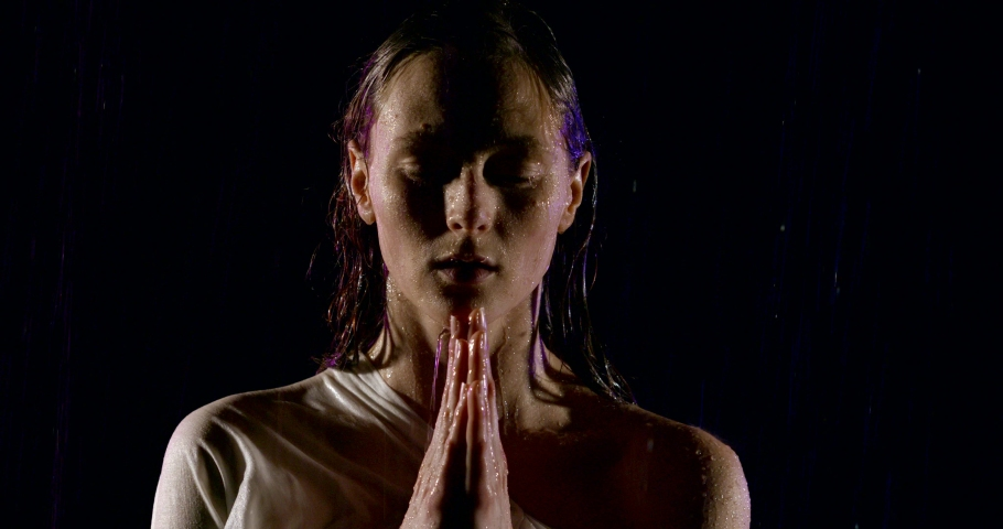 sad woman is standing with folded hands on chest under water flows in darkness, worshipping