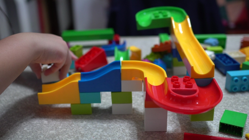 Little child playing the track made of blocks.With lots of colorful plastic toys indoor. | Shutterstock HD Video #1031226209