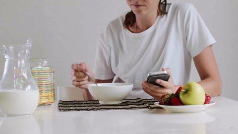 Woman is eating her breakfast cornflakes with milk listening music in earphones. Simultaneously she is browsing mobile phone sitting at table on white background.
