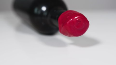 Closeup of a dusty very old bottle of wine with a manual made seal from red wax. Laying on a white table with a white background.