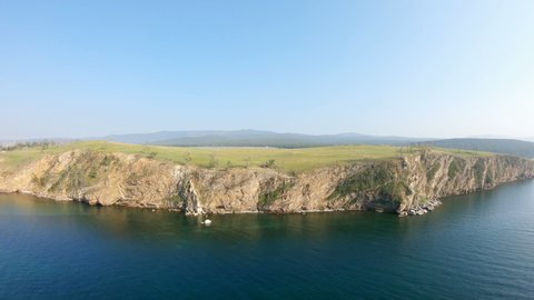 Drone is flying forwards over the sea and the steep rocky coast. Aerial view of Olkhon island, lake Baikal