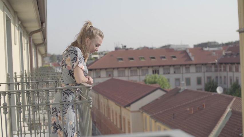 Young tourist woman on hotel balcony in the morning. Pretty blonde girl in a dress enjoying the european city view. Sightseeing, exploration, destination and adventure concept. | Shutterstock HD Video #1031512439