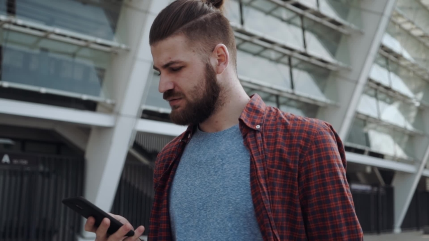 Bearded Man talking on a phone. Casual professional entrepreneur using smartphone smiling outside. Outdoor portrait of modern guy with mobile in the street. | Shutterstock HD Video #1031686949