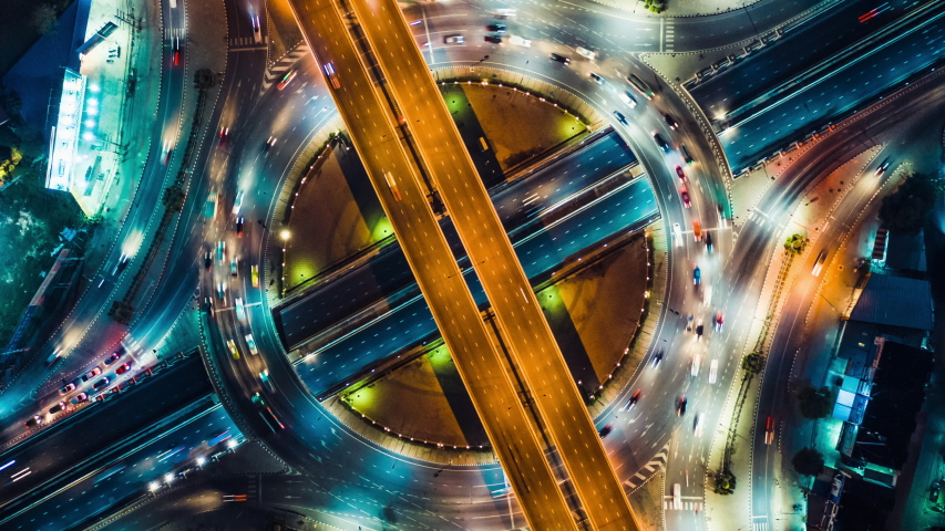 Beautiful top view time-lapse of car traffic at roundabout lane and buildings. 4K drone aerial zoom out. Urban cityscape concept or abstract of advanced innovation, financial technology, energy power