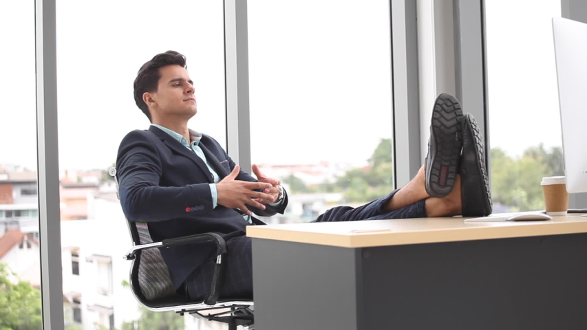 Business man relaxing or sleeping after finished work put  feet on the desk in office. male boss worker close eyes sitting with legs on the table in the resting time at work place