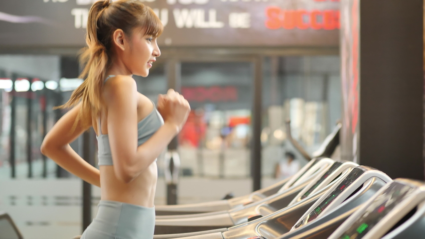Young beautiful woman asian running on a treadmill at gym. Fitness and healthy lifestyle concept. Side view of girl in sportswear jogging exercise. Slow motion | Shutterstock HD Video #1031891549