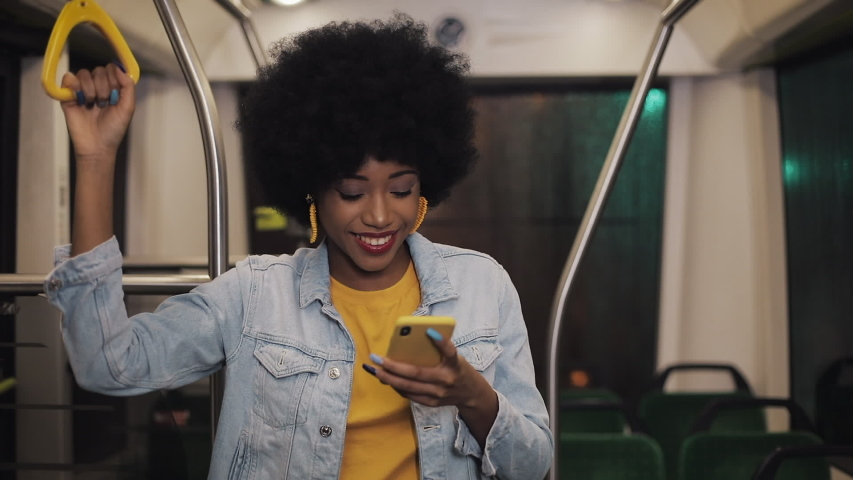 Smiling young african american woman holds the handrail and watching video on the smartphone at public transport. Night time. Close-up. City lights background. | Shutterstock HD Video #1031896589
