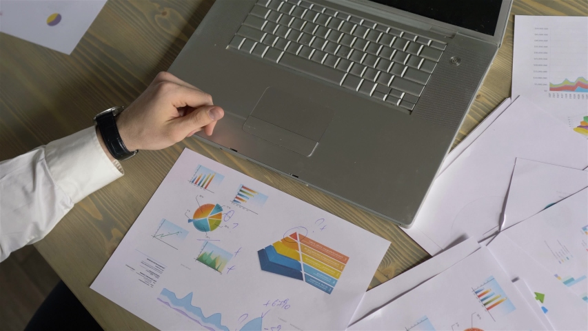 Businessman hands make notes on paper with graphs | Shutterstock HD Video #1031935499