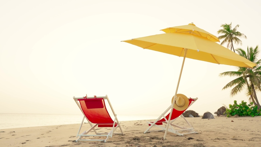 Beach beds and sun umbrella on palm trees coast. Aurora on amazing isle. Atlantic ocean, wild palms isle beach, bright yellow cockcrow. Beach beds, sun umbrella, nature landscape postcard. Copy space | Shutterstock HD Video #1032012329