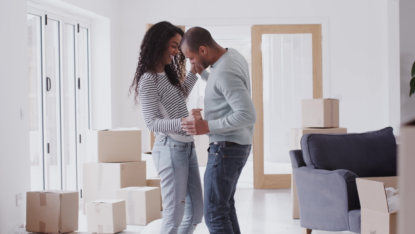 Loving Couple Dancing Together As They Celebrate Moving Into New Home #1032046169