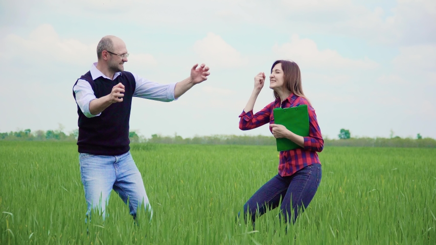 Two happy and funny farmer agronomist with papers rejoice jump and laugh on green wheat field waving head and hair fluttering. Business meeting male and female on agricultural land | Shutterstock HD Video #1032068609