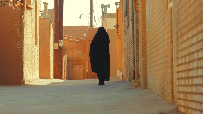 Muslim woman in traditional chador walking on street in Old city of Yazd, Iran  | Shutterstock HD Video #1032074909