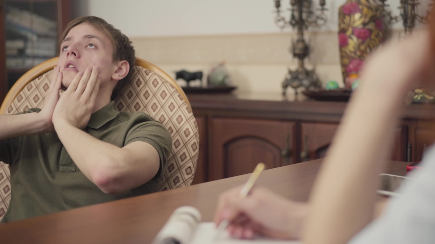 Portrait young guy at a session with a psychotherapist. The teenager talks about his problems and fears to the psychologist. | Shutterstock HD Video #1032078629
