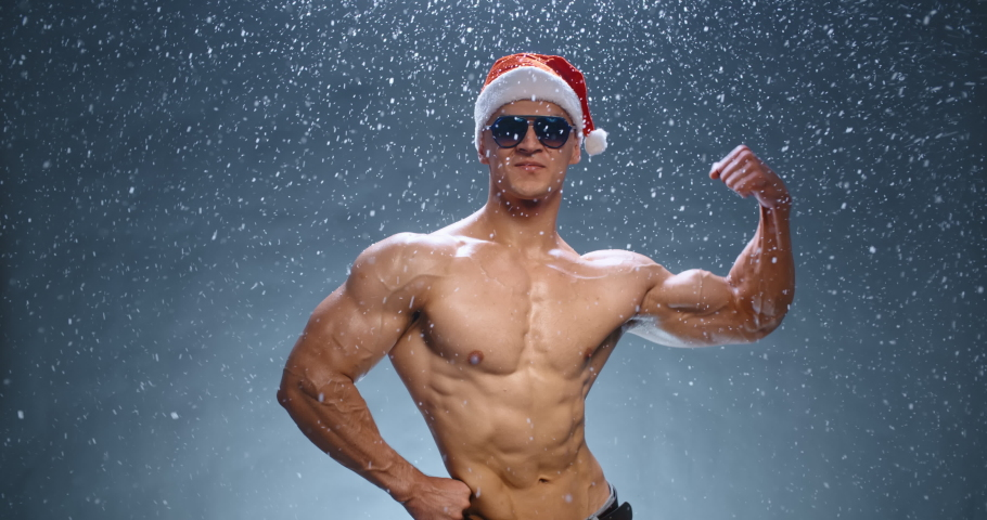 Cool Young asian bodybuilder in christmas hat wearing sunglasses looking at camera and showing of his huge muscles, isolated over blue background - holiday mood concept close up 4k footage
