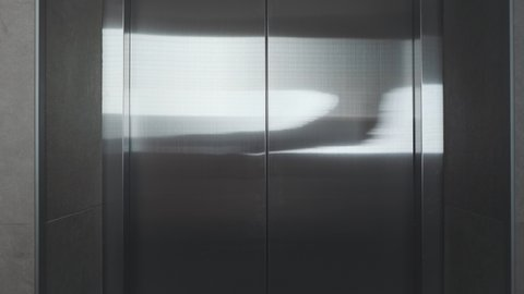 The elevator doors open. Opening the door is an elevator. Metal doors smoothly open and close. Silver new elevator on the 1st floor 4k video.