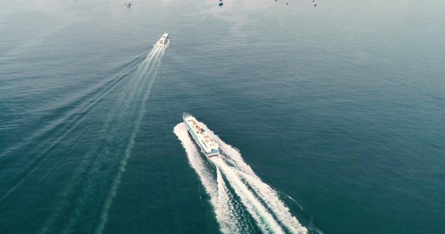Speed boat on the sea with wake foam on blue water. High-quality stock video footage view from above, top view of cruise ship moving on the beach with ocean waves and sea foam to island | Shutterstock HD Video #1032268859